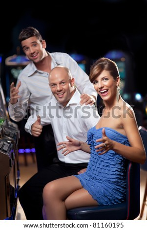excited woman winning at the slot machine, with happy friends cheering - stock photo
