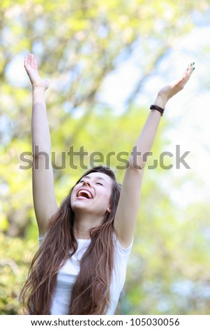 Excited woman with arms raised - stock photo