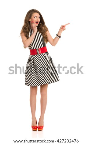 Excited woman with long brown hair wearing black and white striped dress and high heels holding hand on chin, looking away and pointing, Full length studio shot isolated on white. - stock photo