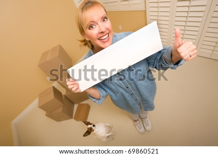 Excited Woman with Thumbs Up and Doggy Holding Blank Sign Near Moving Boxes in Empty Room Taken with Extreme Wide Angle Lens.
