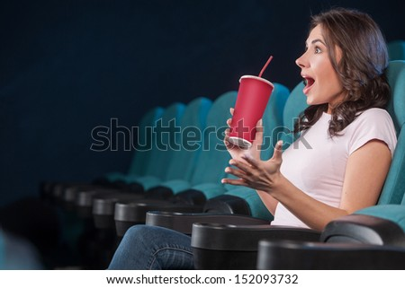 Excited women at the cinema. Side view of beautiful young women drinking soda and gesturing while watching movie at the cinema - stock photo