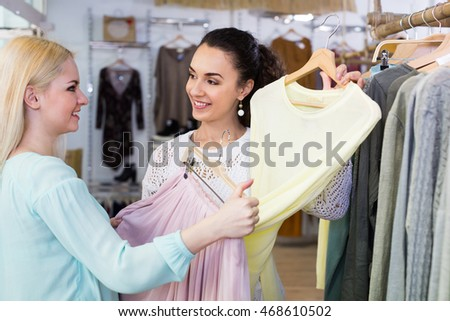 Excited women choosing pullover and skirt at the apparel store