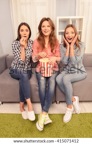 Excited women sitting on couch and watching video with popcorn - stock photo