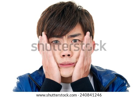 Excited young Asian man with hands to face and surprised expression