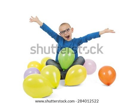 Excited young boy surrounded by balloons against a white background - stock photo
