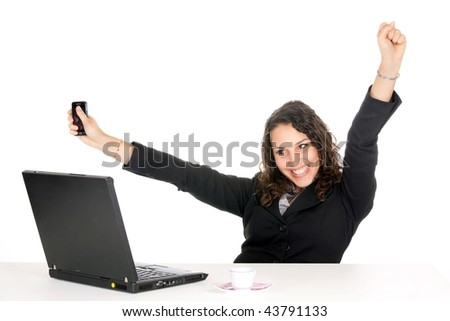 excited young business woman at office with laptop and holding cellphone