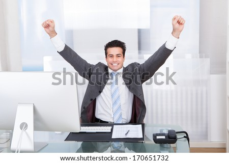 Excited Young Businessman Raising His Hands In Joy - stock photo