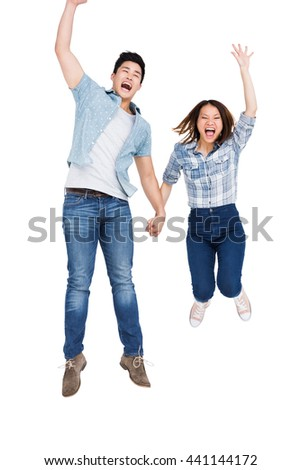 Excited young couple holding hands and jumping on white background - stock photo