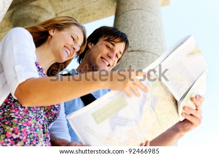 excited young couple traveling, they look at a map while visiting an old tourist attraction monument - stock photo
