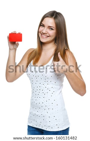 Excited young female showing blank credit card and giving thumb up, isolated on white background - stock photo