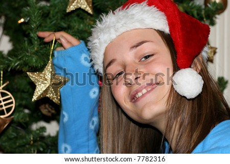 Excited young girl in a red festive hat decorating a christmas tree.