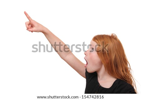Excited young girl points up on white background - stock photo