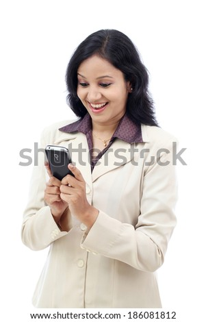 Excited young  Indian business woman text messaging against white