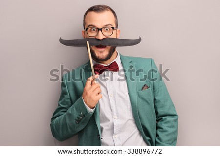 Excited young man in green coat posing against a gray wall and holding a fake mustache on his face - stock photo