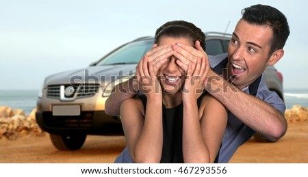 Excited young man with a surprise gift of a motor car for his girlfriend