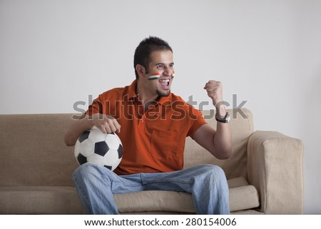 Excited young man with soccer ball cheering while sitting on sofa at home - stock photo