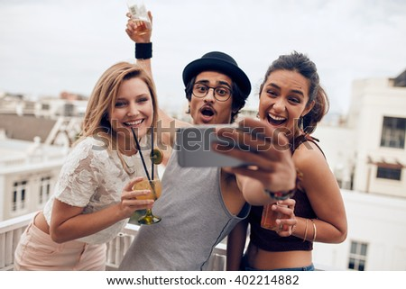 Excited young people taking self portrait with mobile phone during a party. Happy young man and woman taking self portrait at rooftop party. Multiracial people having fun in party with drinks. - stock photo