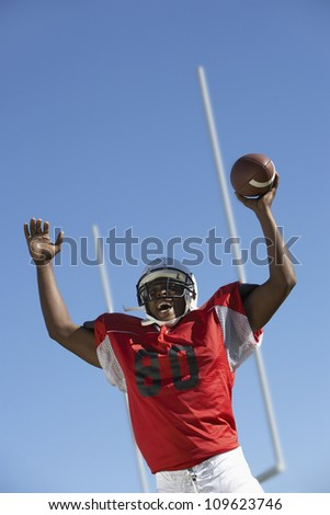 Excited young player holding football ball against sky - stock photo