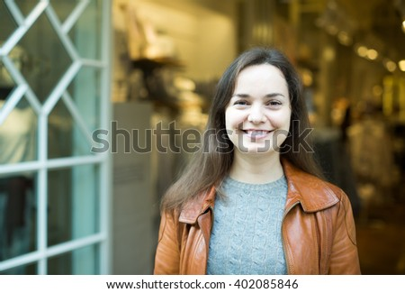 Excited young spanish brunette posing in clothing store and smiling - stock photo