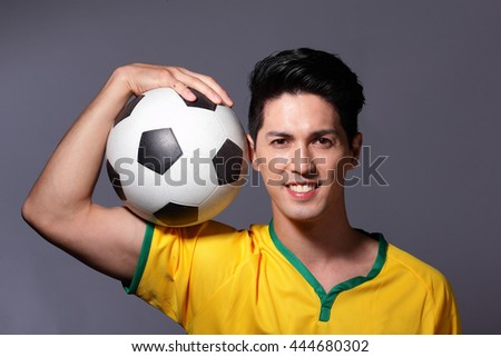 Excited young sport man holding soccer isolated on gray background