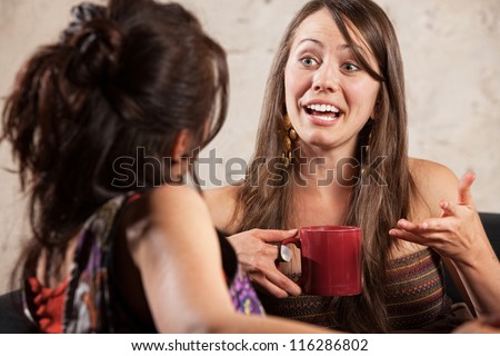 Excited young white woman talking with friend - stock photo