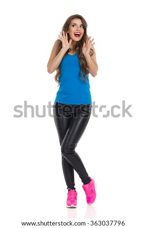 Excited young woman in blue shirt, black leather trousers, and pink sneakers standing with arms raised and shouting. Full length studio shot isolated on white. - stock photo