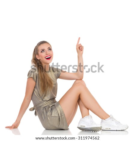 Excited young woman in gold mini dress and white sneakers sitting on a floor, pointing up and looking. Full length studio shot isolated on white. - stock photo