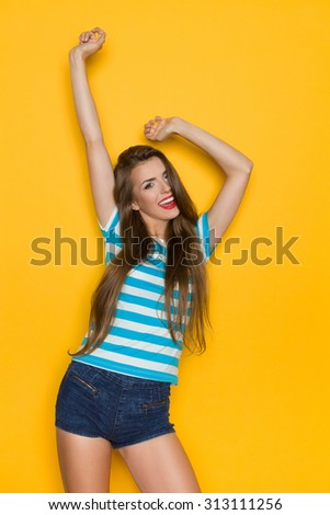 Excited young woman in striped shirt and jeans shorts posing with arms raised. Three quarter length studio shot on yellow background. - stock photo