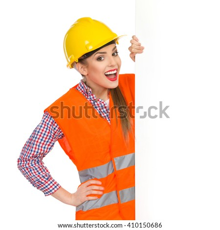 Excited young woman in yellow hardhat, orange reflective vest and lumberjack shirt standing behind big white banner and holding it. Waist up studio shot isolated on white. - stock photo