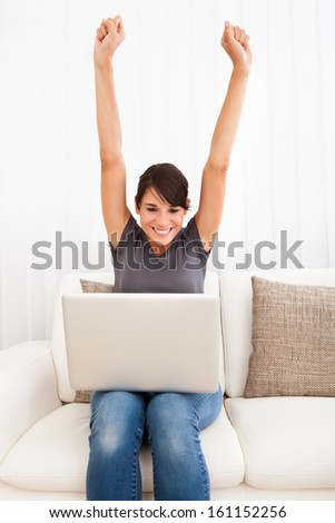 Excited Young Woman Sitting With Laptop On Couch