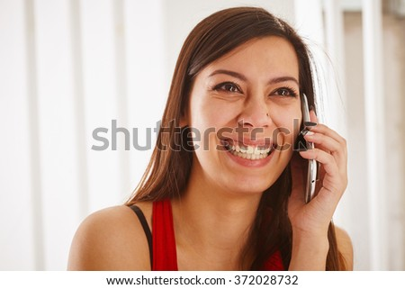 Excited young woman talking on the phone, close up. - stock photo