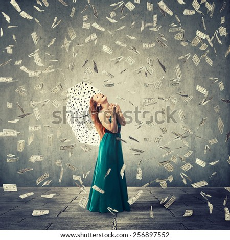 Excited young woman with umbrella under a money rain isolated on grey wall background. Positive emotions financial success luck good economy concept  - stock photo