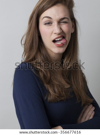 excitement and humor concept - gorgeous young woman playing goofy,making a funny face,standing with arms crossed,studio shot - stock photo