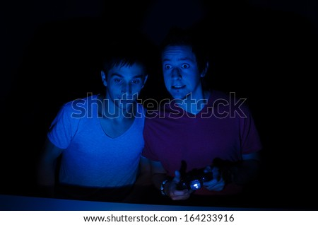 Excitement in front of a screen while playing video games - stock photo