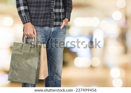 Exciting young shopping man hold bags, closeup portrait with copyspace. - stock photo