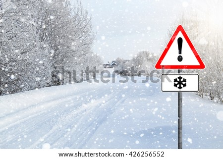 Exclamation point, road sign warning snowfall, village, countryside, rural road, snow-covered road.  secluded village, fabulous landscape frosty sunny day. - stock photo