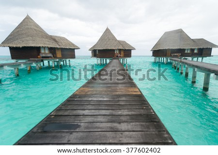 Exclusive luxury resorts pile houses floating on crystal clear turquise waters of ocean, Maldives