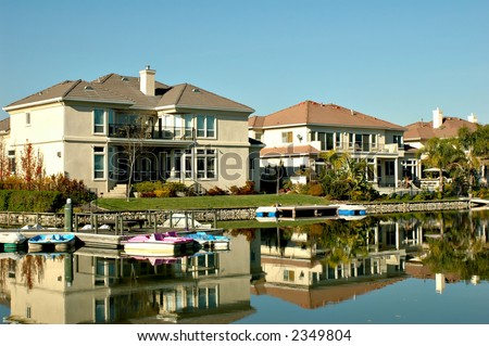 Exclusive waterfront homes on a private lake with boats - stock photo
