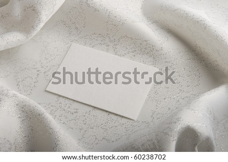 Exclusive white  silver fabric with greeting card. - stock photo