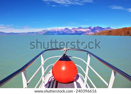 Excursion on the tourist boat on Lake Viedma.  White-blue huge icebergs float near a ship board. Ice and sun Patagonia - stock photo