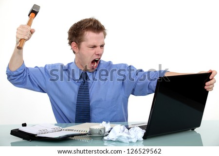 Executive about to smash his laptop with a hammer. - stock photo