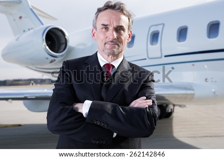 executive business man in front of corporate jet - stock photo
