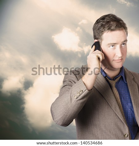 Executive business man standing outdoors against a cloud background on cell phone