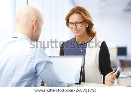 Executive businessman giving advise to business woman while working with laptop at office. - stock photo