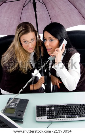 executive busy on phone call and her employee holding umbrella in office - stock photo