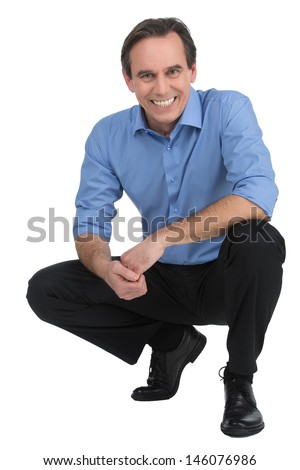 Executive crouching. Cheerful mature businessman sitting crouched and looking at camera while isolated on white - stock photo