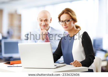 Executive financiers working together on laptop while sitting at office.  - stock photo