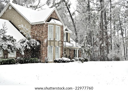 Executive home covered with a white snow blanket on a cold winter day. - stock photo