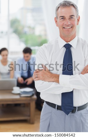 Executive in cosy meeting room standing on foreground with colleagues on background - stock photo