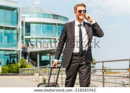 Executive on the Go. Handsome young businessman in full suit carrying suitcase and talking on the mobile phone while walking outdoors - stock photo